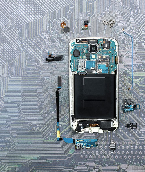 cell phone lies on a circuit board and is broken down into individual parts