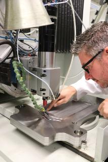 Udo Eckert, Gruppenleiter Mikrosystemfertigung, aus der Abteilung Funktionsoberflächen/Mikrofertigung am Fraunhofer IWU prüft im Mikro-Bearbeitungszentrum des IWU die Finish-Bearbeitung eines gefrästen Werkzeugs für den Einsatz bei der Bipolarplattenfertigung für Brennstoffzellen.
